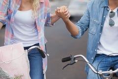 Los pares jovenes de la cadera que van para una bici montan Fotos de archivo libres de regalías