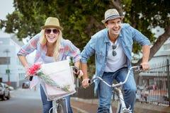 Los pares jovenes de la cadera que van para una bici montan Foto de archivo libre de regalías