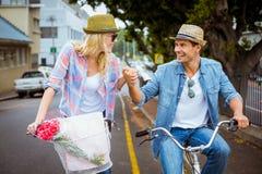 Los pares jovenes de la cadera que van para una bici montan Imágenes de archivo libres de regalías