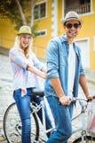Los pares jovenes de la cadera que van para una bici montan Foto de archivo