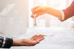 Los pares jovenes de la familia compran las propiedades inmobiliarias de la propiedad del alquiler Agente que da la consulta al h imagenes de archivo