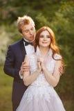 Los pares jovenes de novia y del novio en una floración cultivan un huerto Fotografía de archivo libre de regalías