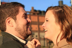 Los pares jovenes de risa se colocan cara a cara Foto de archivo