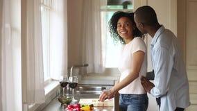 Los pares jovenes del africano feliz celebran aniversario preparan la ensalada vegetal sana almacen de metraje de vídeo