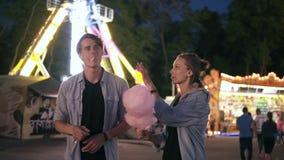 Los pares jovenes del inconformista están teniendo tiempo junto en el parque de atracciones en la noche Alimentación con el caram metrajes