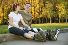 Los pares jovenes del rodillo se sientan Foto de archivo