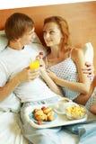 Los pares jovenes desayunan en cama Foto de archivo