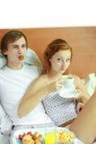 Los pares jovenes desayunan en cama Foto de archivo libre de regalías