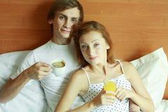 Los pares jovenes desayunan en cama Imagen de archivo libre de regalías