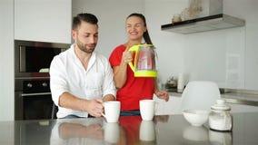 Los pares jovenes desayunan en cocina moderna Taza del café con leche Desayuno en la mañana Esposa y marido felices romántico metrajes