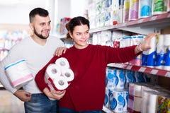 Los pares jovenes eligen el papel higiénico en la tienda Fotos de archivo libres de regalías