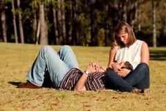 Los pares jovenes en amor comparten un momento cariñoso en parque Imagen de archivo libre de regalías