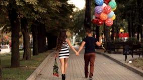 Los pares jovenes en amor con los globos dan un paseo a través del parque almacen de metraje de vídeo