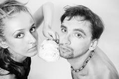 Los pares jovenes en amor con una rosa y una plata blancas construyen Foto de archivo