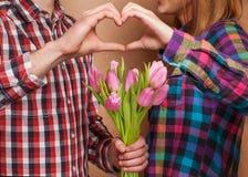 Los pares jovenes en amor hacen un corazón y las manos están sosteniendo tulipanes. Fotografía de archivo