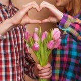 Los pares jovenes en amor hacen un corazón y las manos están sosteniendo tulipanes. Foto de archivo