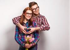 Los pares jovenes en amor hacen un corazón y las manos están sosteniendo tulipanes. Foto de archivo libre de regalías