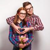 Los pares jovenes en amor hacen un corazón y las manos están sosteniendo tulipanes. Fotos de archivo