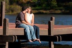 Los pares jovenes en amor se sientan descalzo en muelle Foto de archivo libre de regalías