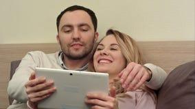 Los pares jovenes en cama utilizan la tableta digital, sonriendo y riendo almacen de video