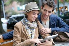 Los pares jovenes en ciudad conectaron con la tableta en cafetería Fotografía de archivo