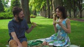 Los pares jovenes en comida campestre del verano parquean para comer los bocadillos, disfrutando del sabor y de la sonrisa almacen de metraje de vídeo