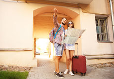 Los pares jovenes en control de visita turístico de excursión de la mujer de la dirección punteaguda del hombre de la ciudad del  Fotos de archivo