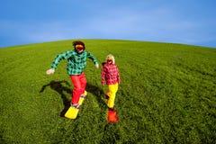 Los pares jovenes en deporte llevan snowboard en la hierba en el gree Imagen de archivo