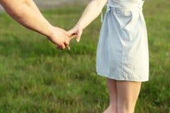 Los pares jovenes en el amor que camina en el otoño parquean llevar a cabo las manos que miran en la puesta del sol Imagenes de archivo