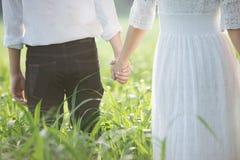 Los pares jovenes en el amor que camina en la primavera colocan llevar a cabo las manos Fotografía de archivo