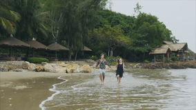 Los pares jovenes en el amor que corre en el mar varan llevar a cabo las manos, la sonrisa y la risa en la cámara lenta El concep metrajes