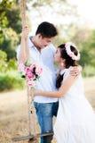 Los pares jovenes en el amor que se sienta en el oscilación y se miran Imagen de archivo libre de regalías