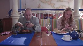 Los pares jovenes en el restaurante pegado en sus teléfonos y se ignoran almacen de video