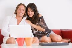 Los pares jovenes en el sofá juegan con el cuaderno Foto de archivo libre de regalías