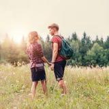 Los pares jovenes en el tiempo de la puesta del sol en bosque caminan Imagen de archivo libre de regalías