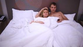Los pares jovenes en la cama que ve la TV, caen dormido almacen de video