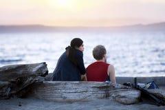 Los pares jovenes en la madera de deriva registran hablar en la playa en la puesta del sol Fotos de archivo libres de regalías