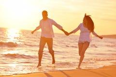 Los pares jovenes en la playa se divierten Imágenes de archivo libres de regalías