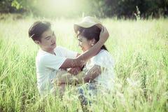 Los pares jovenes en la sentada del amor y se miran en el prado Foto de archivo