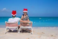 Los pares jovenes en los sombreros de Papá Noel durante la playa vacation Imágenes de archivo libres de regalías