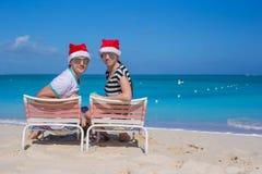 Los pares jovenes en los sombreros de Papá Noel durante la playa vacation Imagen de archivo