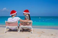 Los pares jovenes en los sombreros de Papá Noel durante la playa vacation Fotos de archivo libres de regalías