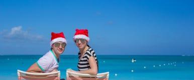 Los pares jovenes en los sombreros de Papá Noel durante la playa vacation Foto de archivo libre de regalías