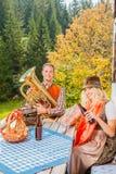 Los pares jovenes en traje bávaro tradicional en el partido en un verano pastan en las montañas Foto de archivo