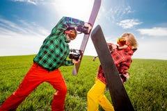 Los pares jovenes en traje de esquí tienen batalla de la diversión con el togethe de las snowboard Imágenes de archivo libres de regalías