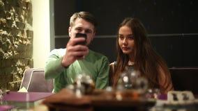 Los pares jovenes en un restaurante hacen el selfie almacen de metraje de vídeo