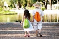 Los pares jovenes entran en parque Fotos de archivo