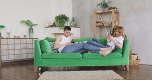 Los pares jovenes están hojeando el sittingon de los smartphones el sofá verde almacen de video