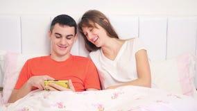 Los pares jovenes están mirando el teléfono almacen de video