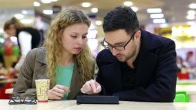 Los pares jovenes están utilizando Tablet PC en cafetería almacen de metraje de vídeo
